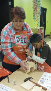 INSTRUCTOR WITH BOY MAKING BIRDHOUSE